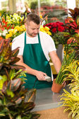 Florist man reading barcode potted plant shop — Stock Photo