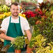 Happy male florist working flower gardening shop - Stock Photo