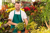 Floreria hombre feliz trabajando en jardinería floristería — Foto de Stock