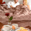 Happy couple lying bed romantic breakfast hotel - Stock Photo