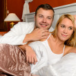 Smiling husband holding wife lying bed married — Stock Photo