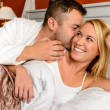 Happy couple bed man giving kiss woman - Stock Photo