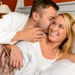Happy couple bed man giving kiss woman - Photo
