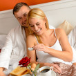 Happy lovers lying bed eating romantic breakfast — Stock Photo