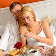 Happy lovers lying bed eating romantic breakfast — Stock Photo #20863689
