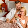Loving couple celebrating romantic anniversary rose bed — Stock Photo #20863757