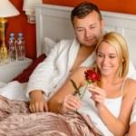 Loving couple celebrating romantic anniversary rose bed — Stock Photo