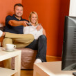 Happy couple watching tv evening changing channels — Stock Photo