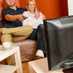 pareja feliz viendo la televisión juntos relajante sofá — Foto de Stock