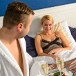 Husband flirting wife bedroom romantic evening celebration - Foto Stock