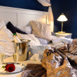 Romantic bedroom rumpled covers hotel champagne bucket - Stock Photo