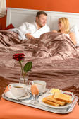Happy couple lying bed romantic breakfast hotel — Stock Photo