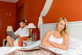 Upset girl sitting bed after fight boyfriend — Stock Photo