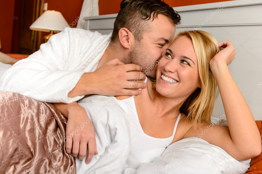 Happy couple in bed man giving kiss woman cheek — Stock Photo #20863315