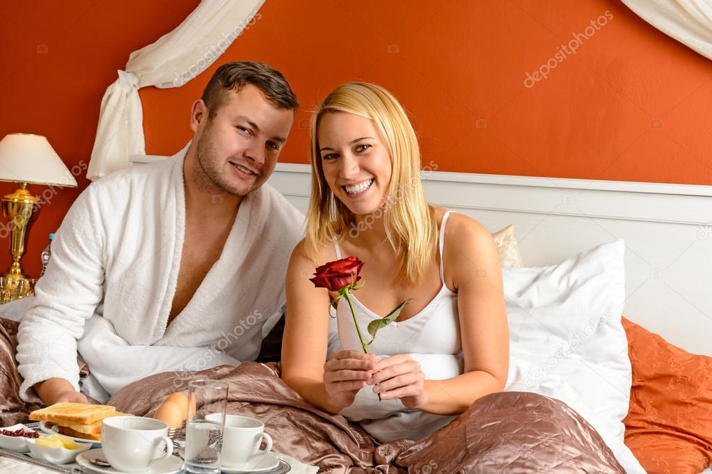 Smiling couple sitting in bed breakfast celebrating Valentine's day — Stock Photo #20863371