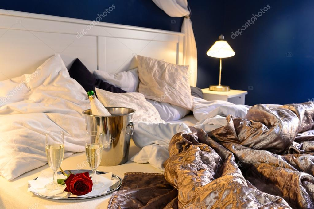 Romantic bedroom rumpled covers luxury hotel champagne bucket — Lizenzfreies Foto #20865699
