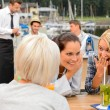 Gossiping women sitting at harbor bar - Stock Photo