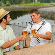 Foto Stock: Cheerful male friends drinking beer at pub