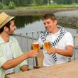 Cheerful male friends drinking beer at pub - Stok fotoğraf