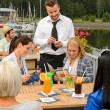 Foto Stock: Waiter taking orders sidewalk bar from women