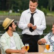Smiling waiter taking order from men customers — ストック写真