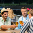 Three male friends drinking beer outdoor terrace — Stok fotoğraf