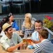 Three men drinking beer at terrace bar — Stock Photo
