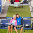 Cuddling couple pointing chair lift in sweatsuits — Stock Photo