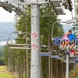 Cuddling couple going through pinewood chair lift — Stock Photo