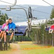 Smiling couples using chair lift scenic landscape — Stock Photo