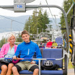 Chair lift going through forest couple sitting — Stock Photo