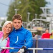 Hugging young couple sitting on chair lift — Стоковая фотография