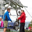 Man helping couple holding bicycle chair lift - Stock Photo