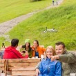 Young tourists in nature sitting bench — Stock Photo