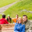 Young tourists drinking refreshments resting wooden bench — Stock Photo #22893506