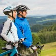 Stock Photo: Smiling cyclists watching scenic view with bikes