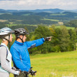 Pointing cyclists couple on summer weekend nature — Stock Photo
