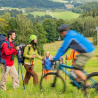 Tourists hiking and riding mountain bikes summer nature — Stock Photo