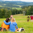 Hiker with camera taking picture resting friends — Stock Photo