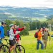 Stock Photo: Hikers helping cyclists following track nature landscape
