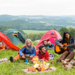Camping students listening girl with guitar tents - Stock Photo