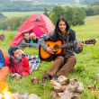 Camping friends lying tents girl playing guitar — Stock Photo