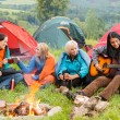 Beside campfire girls sitting listening to guitar — Stock Photo