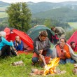 Sitting by campfire friends in tents chatting - Stock Photo