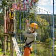 Woman climbing rope ladder in adventure park - Stok fotoğraf