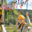 Woman climbing on rope ladder adrenalin park — Stock Photo #22893874