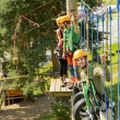 Climbing visitors in adventure park - Stock Photo