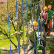 Smiling man climbing in adventure park - Stockfoto
