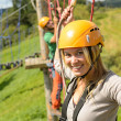 Woman with helmet smiling in adventure park — Stock Photo