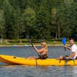 On pond young couple sitting in kayak — Stock Photo #22893982